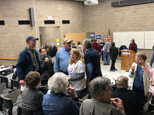 Marit Veltri hands out Kringla to supporters of former Vice President Joe Biden at one of the Palo Alto Democratic caucus in Emmetsburg Monday night.
