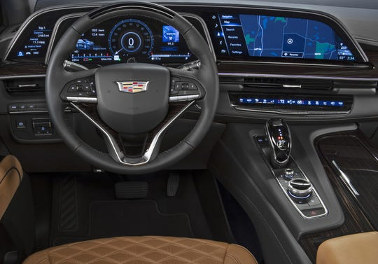 The 2021 Cadillac Escalade's instrument panel consists of three screens stretching 38 inches, from near the driver's window past the middle of the SUV.