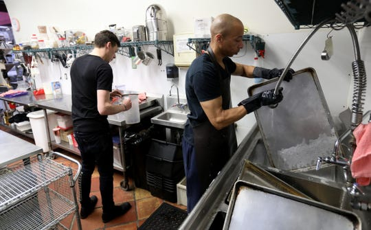 Malachi Muhammad, right, washes a cookie sheet at The Lunch Room Bakery & Cafe in Ann Arbor on Tuesday, Feb. 4, 2020. Muhammad, a former juvenile lifer, was released from prison in November after 29 years incarcerated. He said the restaurant's owner, Phillis Engelbert, was the first person to take a chance on him.