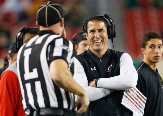 Cincinnati coach Luke Fickell and line judge Dan Bush share a laugh during the second half against South Florida, Tampa, Fla. on Nov. 16, 2019.