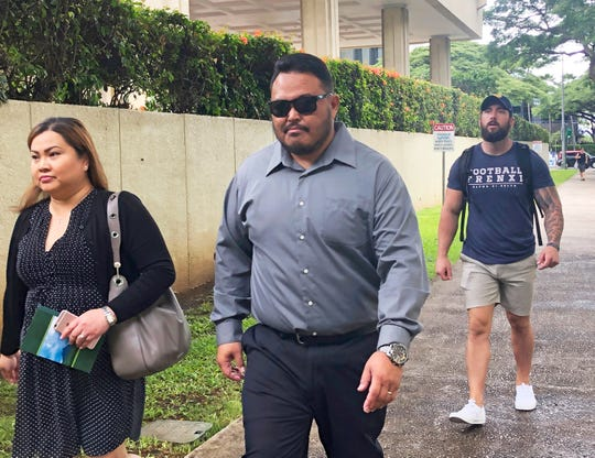 FILE - In this Sept. 25, 2019 file photo, former Honolulu police officer Reginald Ramones, center, walks down a street in Honolulu.