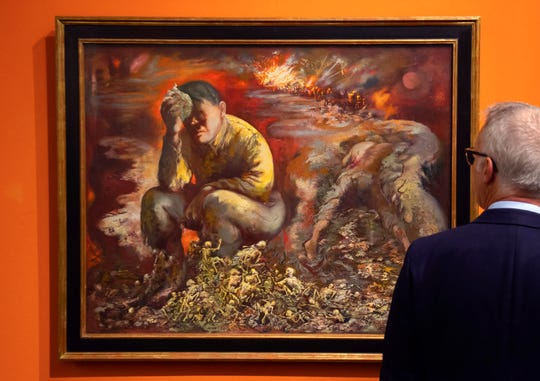 """A man looks at a 1944 painting """"Cain or Hitler in Hell"""", by George Grosz, during a press preview at the German Historical Museum in Berlin, Germany, Tuesday."""