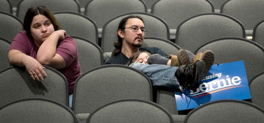 Jeff Lopez holds his son, Tristan, 4, as they and Jeff's wife, Jessika, sit in an area for Bernie Sanders supporters during the Woodbury County Third Precinct Democratic caucus, Monday at West High School in Sioux City, Iowa. Iowans across the state attended Democratic and Republican caucuses Monday.