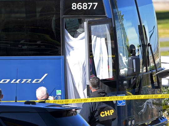 Coroner's officials work behind a drape to remove the body of a person who was killed when a gunman opened fire aboard a packed Greyhound bus, and wounded five others before the driver pulled over onto the shoulder and the killer got off, in Lebec, Calif., some 75 miles north of Los Angeles, Monday.