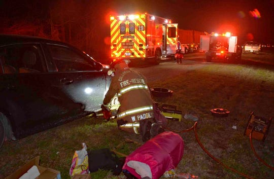 A member of the Colleton County, N.C., fire-rescue uses a tool to lift a woman's car Sunday, Feb. 2, 2020. The woman called 911 with her toes after her hands were crushed while changing a flat tire.