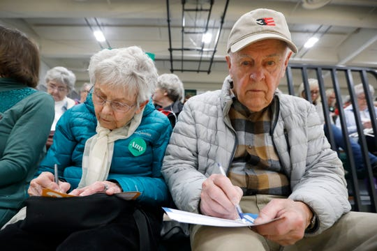 Lenora and Norman Iverson, of Des Moines, Iowa, fill out their Presidential Preference Cards during a Democratic party caucus at Hoover High School, Monday, Feb. 3, 2020, in Des Moines, Iowa.