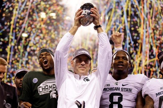 In this Dec. 5, 2015, file photo, Michigan State coach Mark Dantonio holds the trophy after Michigan State defeated Iowa 16-13 in the Big Ten championship game in Indianapolis.