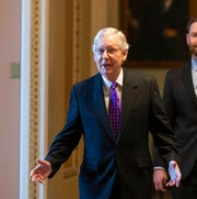 Senate Majority Leader Mitch McConnell of Ky., left, walks from the Senate Floor on Capitol Hill, Tuesday, Feb. 4, 2020 in Washington.