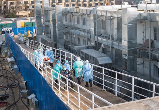 In this photo released by China's Xinhua News Agency, medical workers in protective suits help transfer the first group of patients into the newly completed Huoshenshan temporary field hospital in Wuhan in central China's Hubei province.