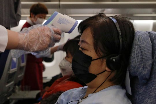 """Stewardesses take temperatures of passengers as a preventive measure for the coronavirus on an Air China flight from Melbourne to Beijing before it land at Beijing Capital International Airport in China, Tuesday, Feb. 4, 2020. China said Tuesday the number of infections from a new virus surpassed 20,000 as medical workers and patients arrived at a new hospital and President Xi Jinping said """"we have launched a people's war of prevention of the epidemic."""""""