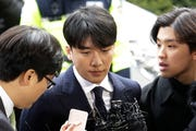 Seungri, center, member of a popular K-pop boy band Big Bang, arrives at the Seoul Metropolitan Police Agency in Seoul, South Korea on March 14, 2019.