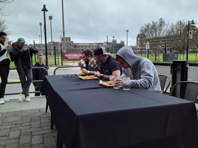 Max Baroody (right), Evan Hamilton and Hunter Harris (left) all race to eat their hundred tots. Baroody was the champion of the competition with Harris and Hamilton earning second and third place.