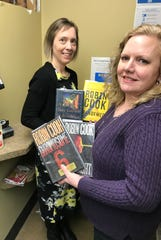 Cathy Kolbeck, left and Carol Petrina, directors of the Algoma and Kewaunee public libraries respectively, show some of the materials ordered from the libraries for pickup at the new Luxemburg Library Station at Stodola's IGA.