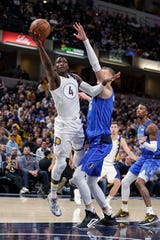 Indiana Pacers guard Victor Oladipo (4) shoots in front of Dallas Mavericks forward Kristaps Porzingis (6) during the second half of an NBA basketball game in Indianapolis, Monday, Feb. 3, 2020. The Mavericks defeated the Pacers 112-103.