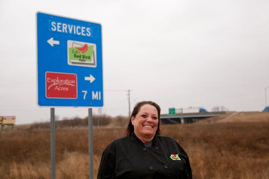 Trish Brown, owner of Thrish's Red Bird Cafe in Dayton, poses next to a service sign on the I-65 north off-ramp to Ind. 38, Tuesday, Feb. 4, 2020 in Dayton.
