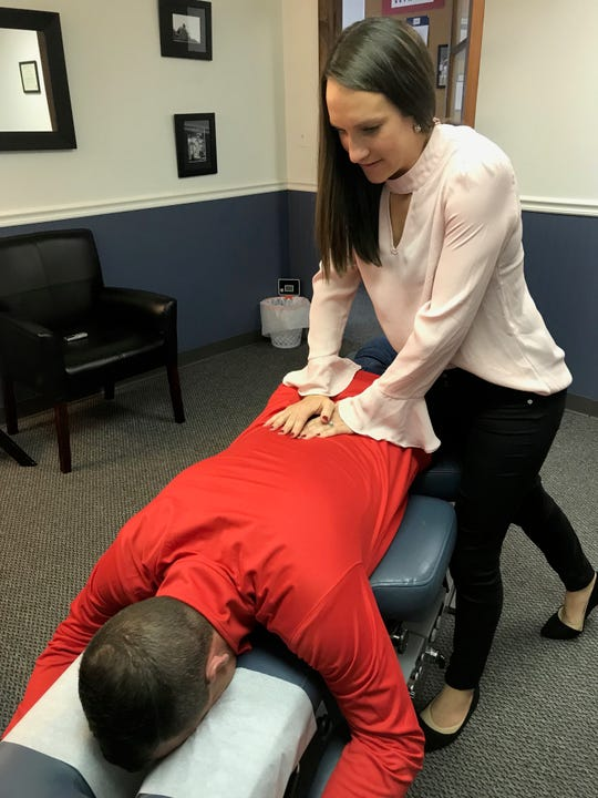 Dr. Kate Bruce, of Bruce Chiropractic, demonstrates a spinal move on her husband, Justin. The couple opened the practice at 118 E. Main St. in March 2016.
