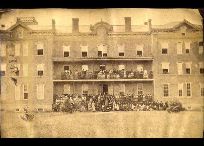 Students and faculty posing outside of the ladies hall at Berea College in the late 1800's.
