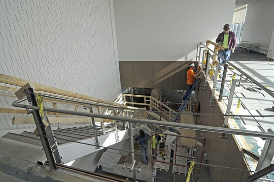Workers install the glass encased stairway from the main entrance to the second floor at University Hospitals Richland Health Center.