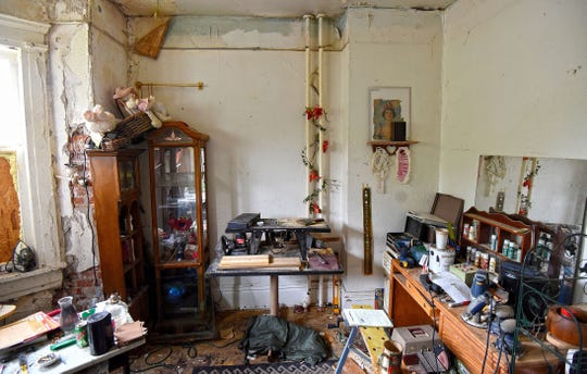 The apartment of Shawn Grate at 132 West 2nd St. is filled with woodworking tools, cigarette butts, stuffed animals and other personal effects in this 2016 file photo. The house was razed on Monday.