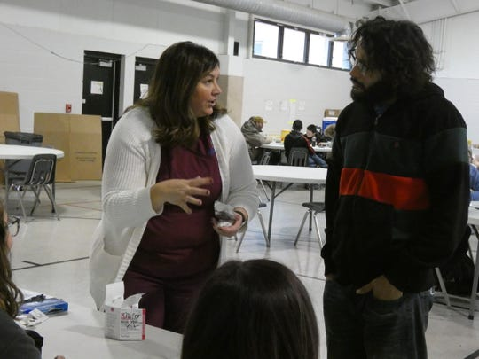 Marion Public Health Director of Nursing Rachel Hill, left, shows Eric Monroe, right, how to use Narcan nasal spray in the event someone is suffering from an opioid overdose. Marion Public Health held a pop-up clinic to distribute Narcan kits at the Salvation Army, 317 W. Church St., Monday.