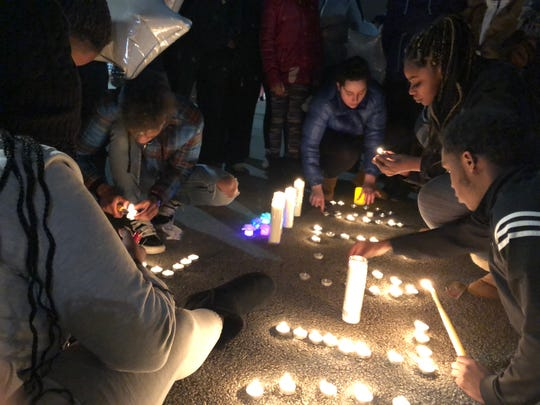 """A vigil was held Monday, Feb. 3, 2020, for Alvin Cole in the same parking lot where he was shot Sunday. Friends and family of Cole light candles here, which spelled out """"Alvin."""""""