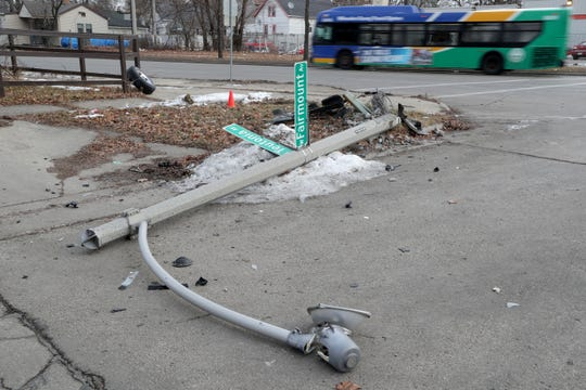 A light pole lays in the road at North Teutonia and West Fairmount avenues in Milwaukee on Tuesday. The damage occurred as a result of a crash involving a vehicle pursuit by police at about 1 a.m. Tuesday morning. An officer was wounded by a suspect during the chase. The suspect was later found dead of a self-inflicted gunshot wound, police said.