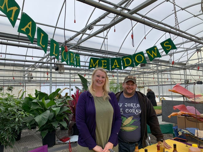 Erica and Zach Mallory stand under their Mallory Meadows sign inside the Thomas Greenhouse near Mukwonago during the winter's farm market Feb. 1. The couple operates a 4-acre farm in the town of Eagle, where they raise produce, chickens, ducks and more. They also have 14 beehives, from which they sell honey.