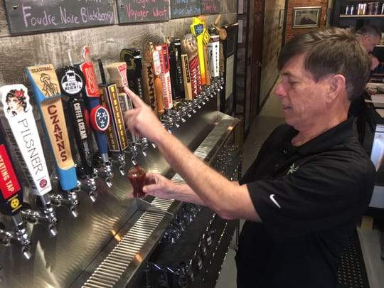 Mark Cook pours a tester of one of his beers for a customer on Feb. 3, 2020.