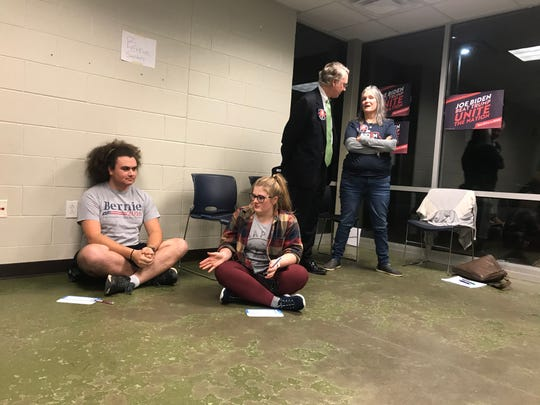 Schyler Davis and Caroline Wilford, who are both registered Iowa Democrats and Bernie Sanders supporter, sit under a sign for their favorite candidate during an Iowa caucus held in Nashville on Monday.
