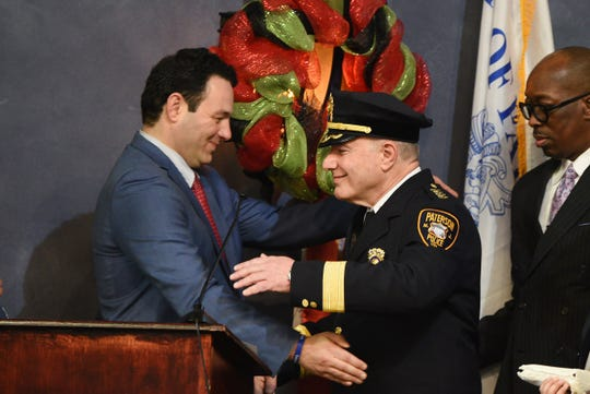 """Paterson Mayor Andre Sayegh embraces Paterson's new Police Chief, Ibrahim """"Mike"""" Baycora, following the Swearing In Ceremony at Council Chambers in Paterson City Hall on 02/04/20. Mitsu Yasukawa/Northjersey.com"""