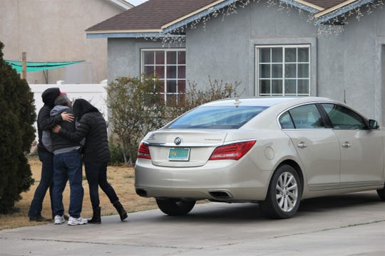 The Parra family console each other Tuesday, Feb. 4, 2020, outside the home on the 400 block of Tierra Dorada Circle in Anthony, New Mexico, where Elvia Martinez de Parra was fatally stabbed the prior evening.