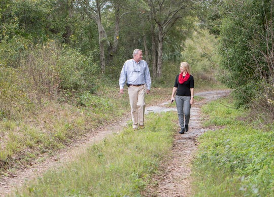 At left, Chips Kirschenfeld, director of Escambia County Natural Resources Management, and Laura Coale, the county's communications director, walk Tuesday along a trail at the Jackson Lakes property off West Navy Boulevard in Warrington. The county is considering turning the property into a public nature trail.