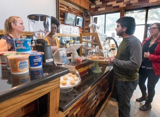 Mido's Coffee Shop owner Kierstyn Hussin, left, takes an order Tuesday from Michael Suhor and Sharee Keener at the shop on North Nineth Avenue in Pensacola.