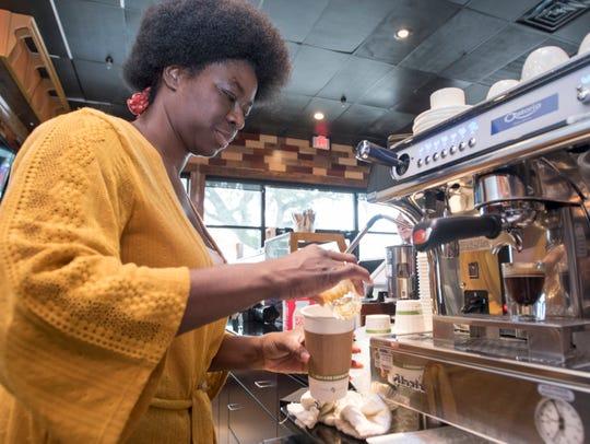 Mido's Coffee Shop barista Rwanda Gresham make a cappuccino Tuesday on North Ninth Avenue in Pensacola.