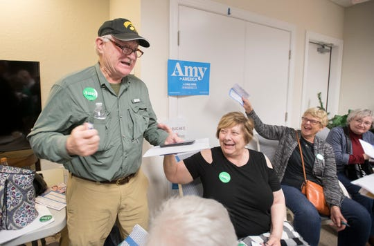 Amy Klobuchar supporters cheer when Stanley Hanus, of Iowa Falls, Iowa, left, switches from supporting Elizabeth Warren to Klobuchar during the second round of the satellite Iowa caucus in Pensacola Beach on Monday, Feb. 3, 2020.