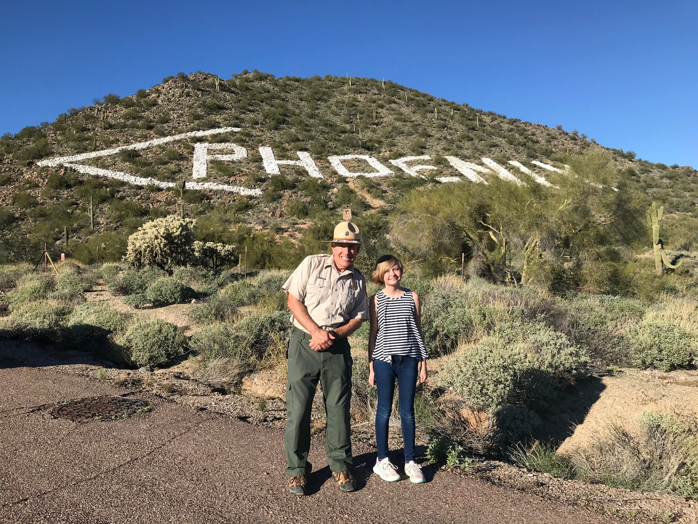 """Brennan Basler, aka """"Ranger B,"""" stands with Lucy Bentz, 12, at Usery Mountain Regional Park. Ranger B shared the story behind the """"<Phoenix"""" sign with Bentz for an episode of Valley 101, an Arizona Republic podcast about metro Phoenix."""