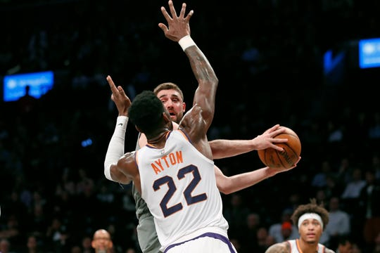 Brooklyn Nets forward Joe Harris, right, looks to pass after being blocked by Phoenix Suns center Deandre Ayton (22) during the first quarter of an NBA basketball game, Monday, Feb. 3, 2020, in New York. (AP Photo/Kathy Willens)