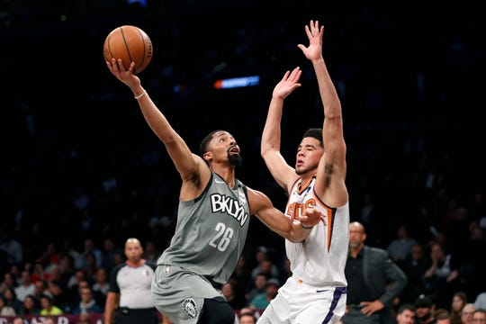 Brooklyn Nets guard Spencer Dinwiddie (26) goes up against Phoenix Suns guard Devin Booker (1) during the first quarter of an NBA basketball game, Monday, Feb. 3, 2020, in New York. (AP Photo/Kathy Willens).