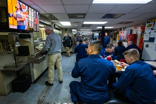 Crewmembers aboard the USCGC Hollyhock watch 'The Price Is Right' as they eat a meal in the ship's mess hall Tuesday, Feb. 4, 2020, on Lake Huron.