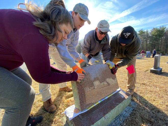 Amy Pitts of Waynesboro, left, is pictured with Jacob Wagaman of St. Thomas, Henry Kendall of Quincy and Eric Smith of South Mountain fixing a fallen headstone Monday morning in Strang Cemetery after it was vandalized Friday.