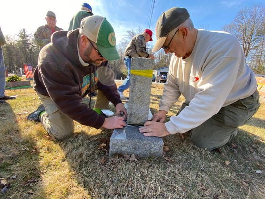 Jim Bowersox and Jason Levick of Grove Bowersox Funeral Home in Waynesboro are pictured replacing a headstone that was pushed off of its base on Monday at Strang Cemetery, which was vandalized Friday.