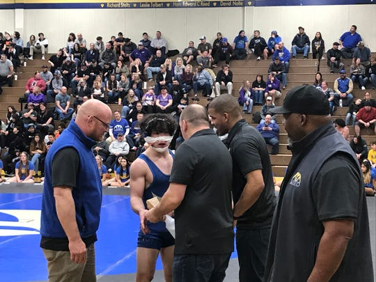 Coaches try to help Reed junior Chance Bustillos after he suffered a bloody nose in the wrestling dual meet against Spanish Springs on Jan. 26.