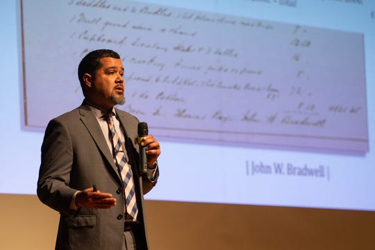 Sean Eversley Bradwell, an assistant professor at Ithaca College, led a discussion on the origins and usage of the N-word at Greece Olympia High School on Monday, Feb. 3, 2020. On the screen behind him is a receipt from when his great-great-grandfather June was sold for $300 in 1852.