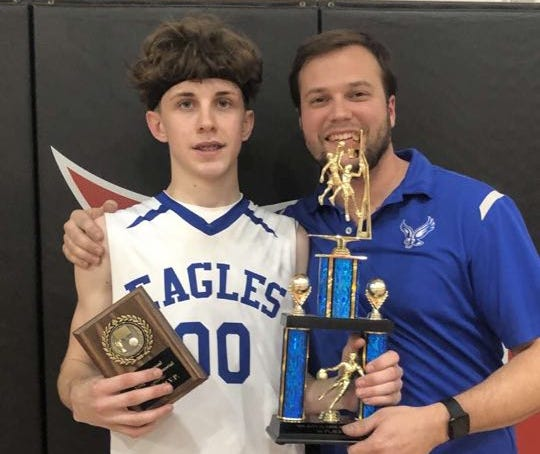 American Christian Academy senior Shawn Sutton holds trophies with coach Brock Fortcamp during the Greg Rust Memorial Tournament held at Simpson College on Dec. 24, 2019.