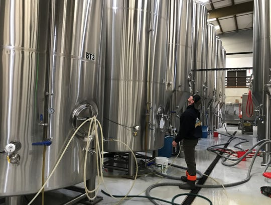 Brandon Keys, packing manager at Fall River Brewing, checks out the tanks inside the brewery.