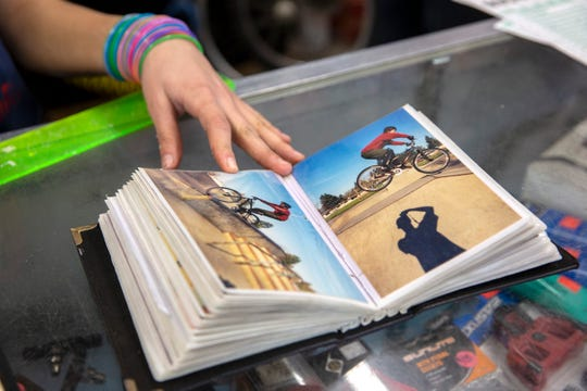 Jaiven Franz thumbs through a photo album, stopping on a picture of her father, at Fall Line Sports in Silverton on January 30, 2020.