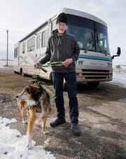 Alan Hallish poses with his dog Coolow by his new temporary motor home that was donated to him, Tuesday, February 4, 2020, in Plymouth, Wis.