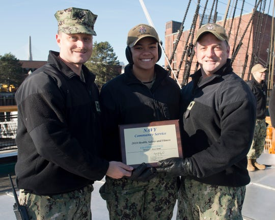 Hospital Corpsman 1st Class Eric Garneau (left), from Port St. Lucie, Seaman Jaida Williams (center), and U.S.S Constitution's Cmdr. Nathaniel R. Shick (right) hold the Navy Community Service Award for Health, Safety and Fitness. (Courtesy of U.S. Navy)