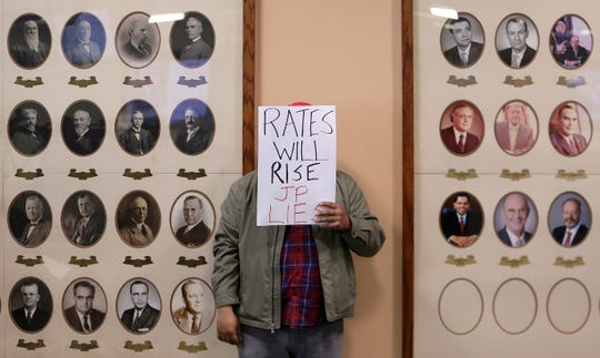 A Sunrise El Paso protestor holds a sign urging El Paso City Council to not allow the sale of El Paso Electric during Feb. 4 meeting.