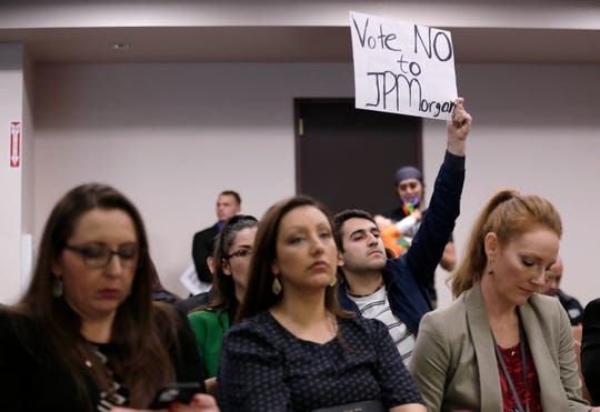 Miguel Escoto, a Sunrise El Paso enviromental group coordinator, holds a sign urging City Council to not allow the transfer of El Paso Electric's city franchise to a JPMorgan-tied investment fund at Council's Feb. 4 meeting.